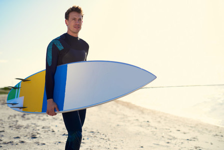 Handsome sporty surfer posing with his surfboard