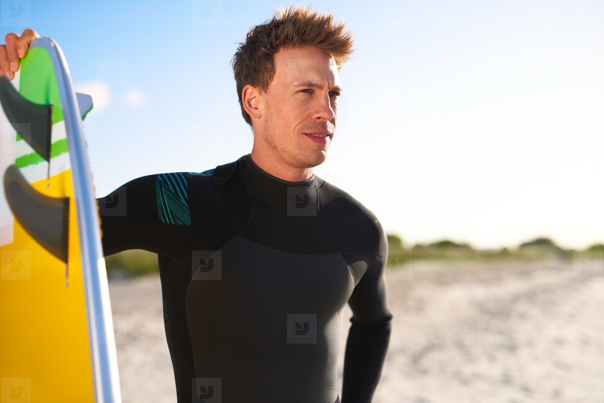 Attractive male surfer assessing the surf