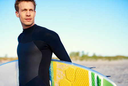 Handsome surfer with a colorful yellow board