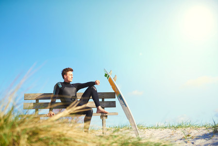 Surfer relaxing on a wooden bench on a dune
