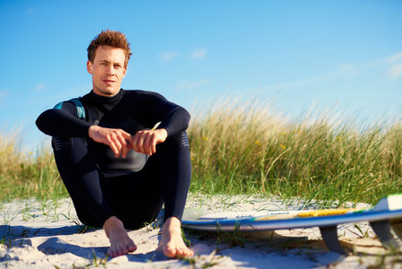 Young surfer relaxing on a dune with his board