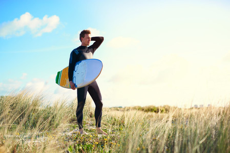 Surfer posing with his board on a sand dune