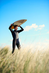 Muscular surfer balancing his board on his head