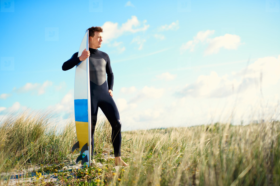 Surfer standing on top of a sand dune