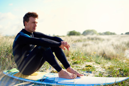 Surfer sitting on his board on a sand dune