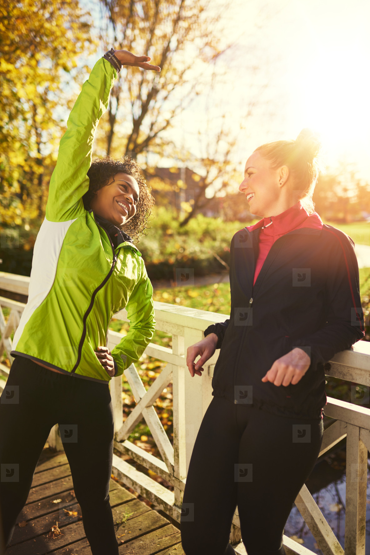 Two smiling sportswomen stretching on bridge
