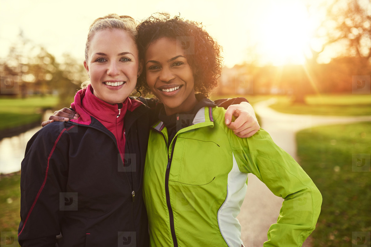 Two girlfriends in sportswear hugging in park