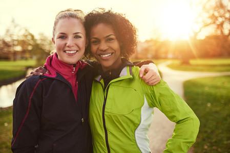 Two girlfriends in sportswear hugging in park
