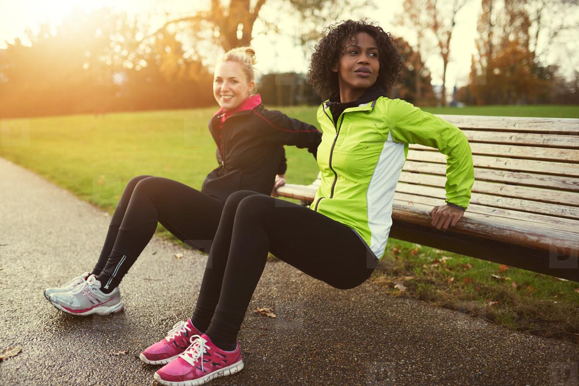 Two sportswomen doing bench dips in park