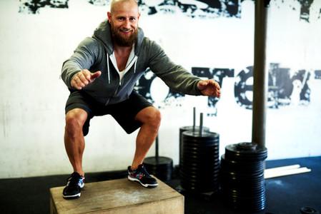 White man smiling at camera doing squats