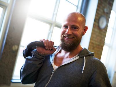Athletic man smiling at camera lifting a kettlebell