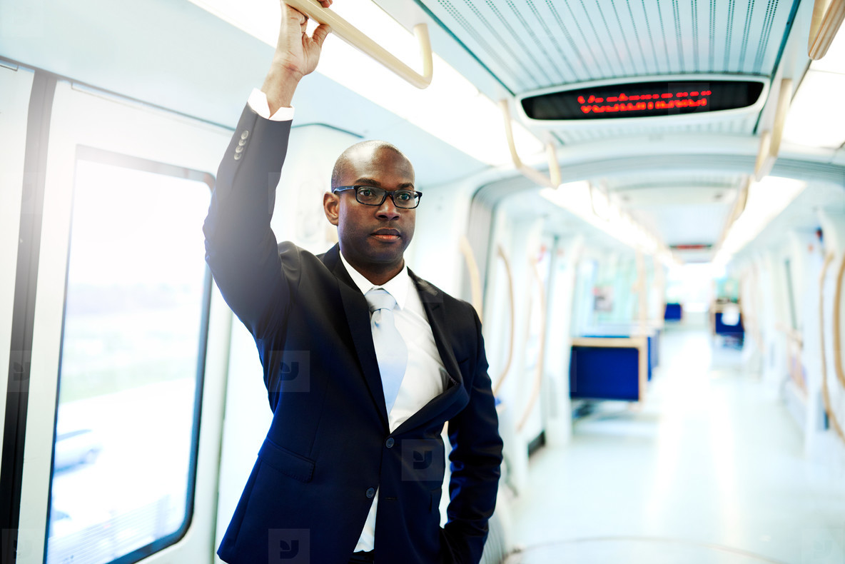 Businessman in a Subway Train Holding on Railing