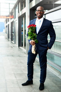 Happy Businessman Waiting at the Metro with Roses