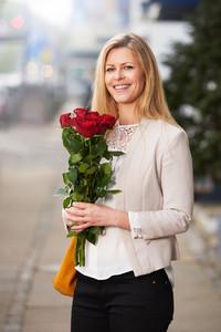Professional woman holding a bouquet of red roses