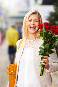 Professional white woman posing on sidewalk holding red roses