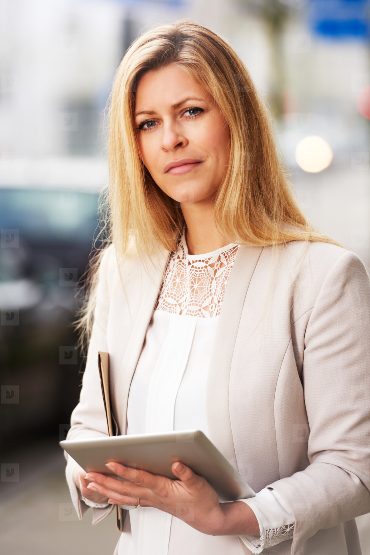 Professional woman posing on sidewalk with tablet
