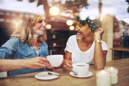 Two multi ethnic friends enjoying coffee