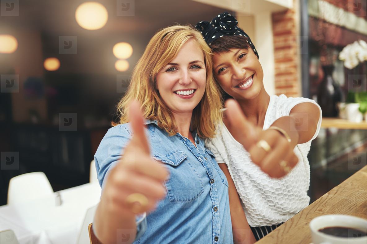 Two happy young female friends giving a thumbs up