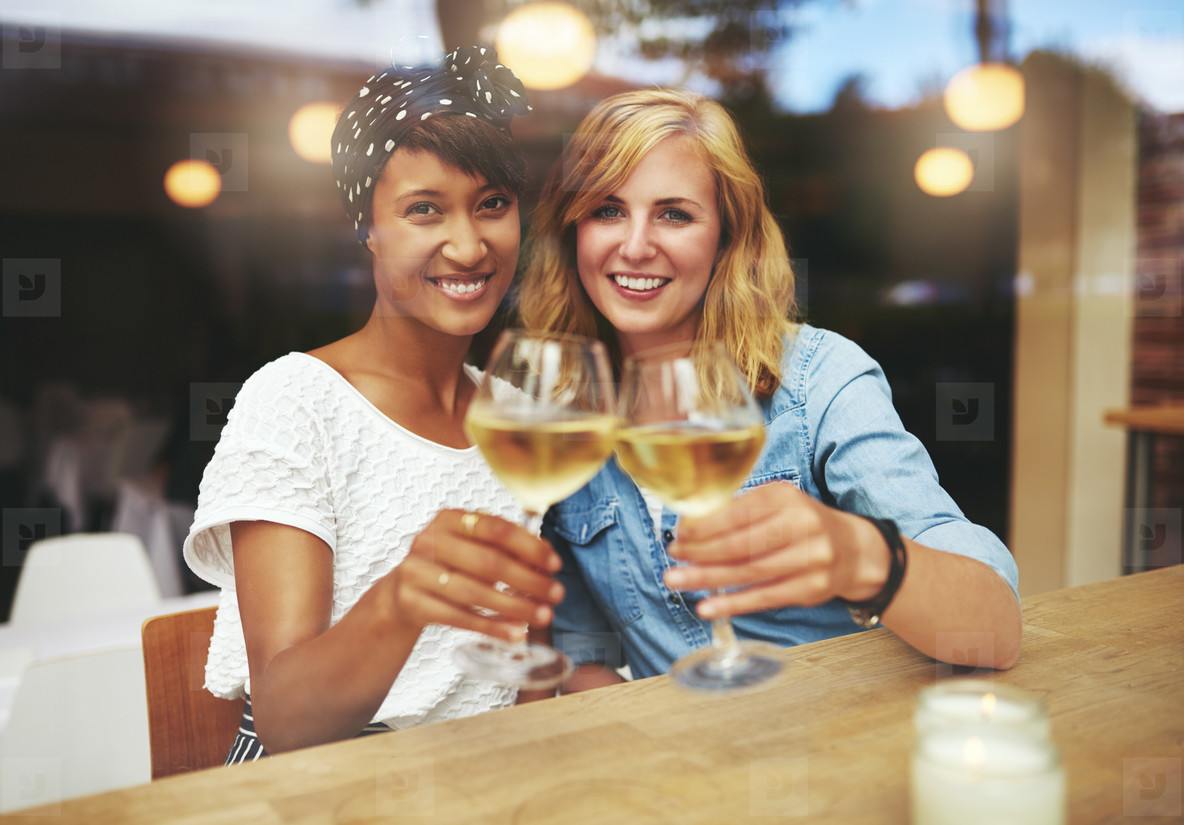Two young women toasting with white wine