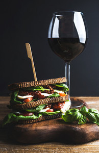 Homemade caprese sandwich and glass of red wine on board