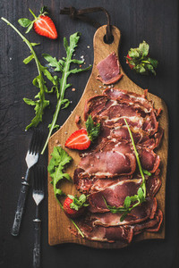 Turkish pastirma with strawberry and arugula on wooden board