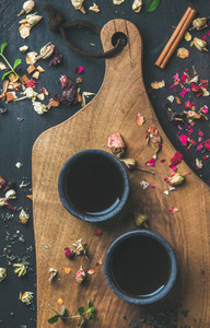 Chinese black tea in black stoneware cups with herbs flowers