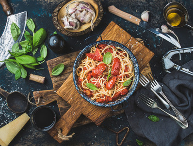 Spaghetti with tomato and basil in plate on wooden board
