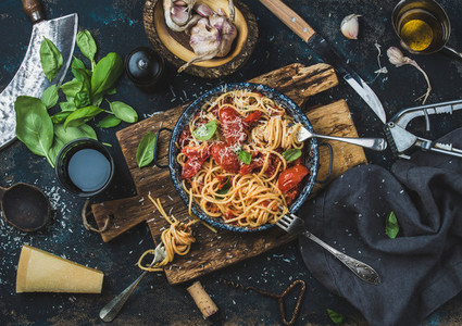 Spaghetti with tomato and basil and ingredients for making pasta
