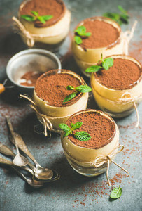 Homemade Italian dessert Tiramisu served in glasses with mint leaves