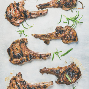 Grilled lamb ribs with fresh rosemary over metal tray background