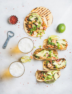 Healthy corn tortillas with chicken  vegetables  limes  beer in glasses