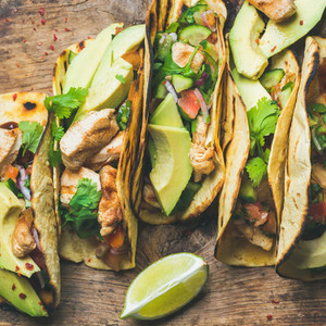 Tacos with chicken  avocado  fresh salsa and limes  square crop