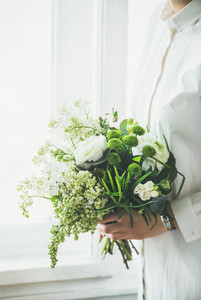 Young woman wearing white clothes holding flowers bouquet