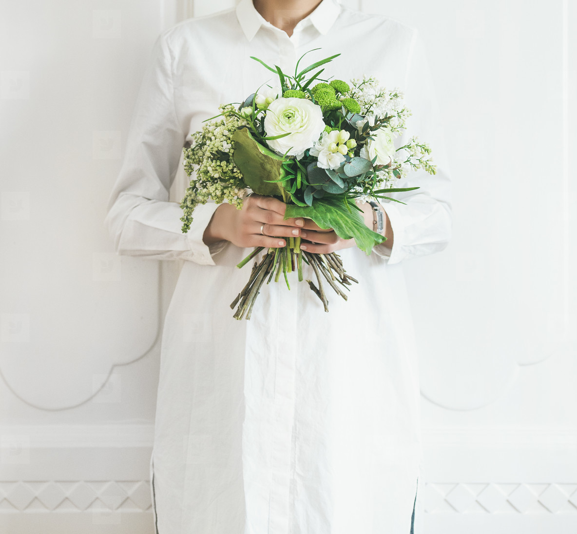 Young woman wearing white clothes holding bouquet  white wall background
