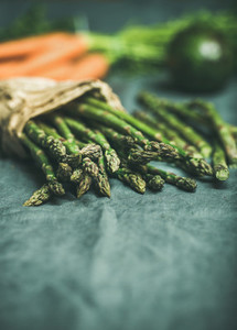 Green asparagus  carrots and avocado at background over linen table