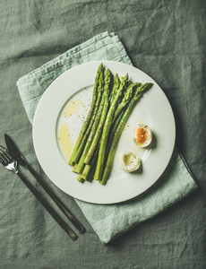 Cooked asparagus with soft boiled egg and herbs grey background