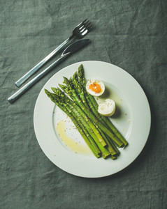 Cooked asparagus with soft boiled egg and herbs on white plate
