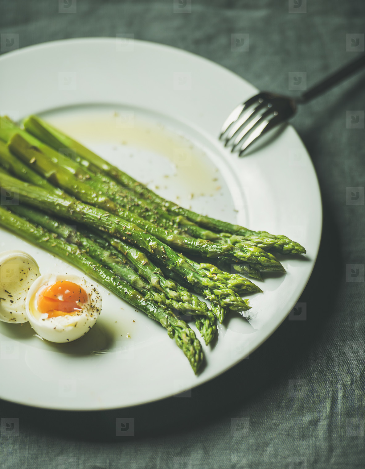Cooked asparagus with soft boiled egg and herbs  selective focus