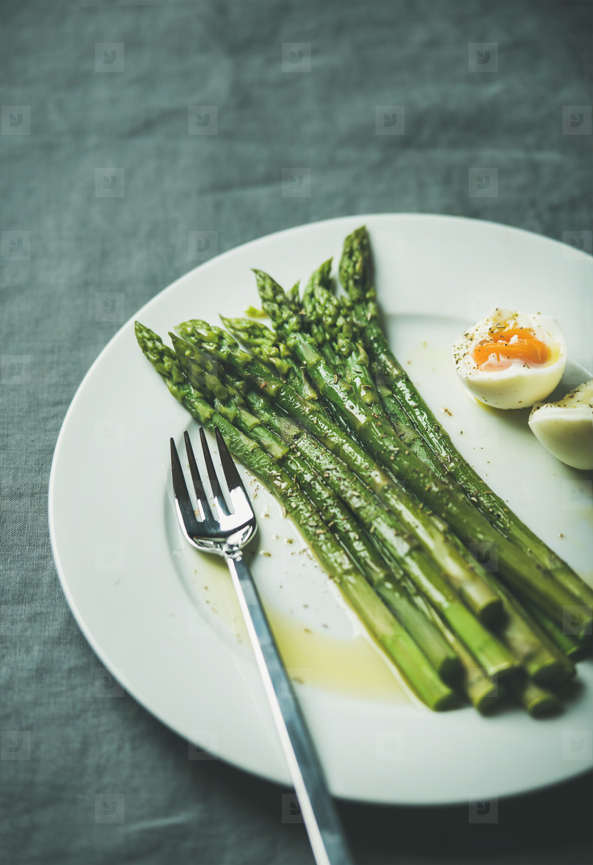 Cooked asparagus with soft boiled egg and herbs  copy space