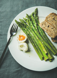 Cooked asparagus with soft boiled egg grilled bread and herbs
