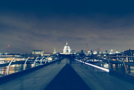 Long exposure on Millennium Bridge at night on London skyline