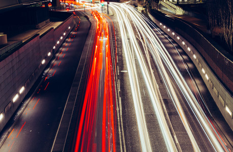 City light trails of fast moving traffic on road in London at ni