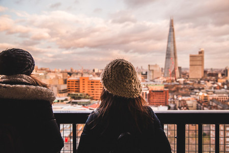 Two young tourist female friends looking at modern London skylin