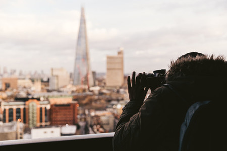 Man taking photo with camera of modern London winter skyline