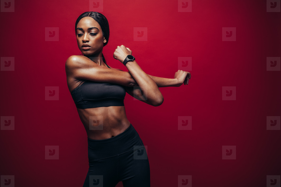 Fit african woman doing stretching exercise