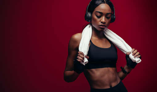 African female athlete listening music after workout