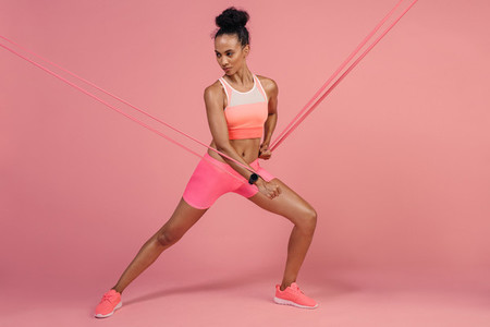 Sportswoman doing stretching exercises with elastic bands