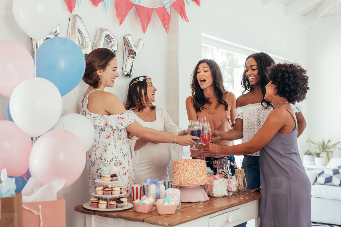 Women toasting with juices at baby shower party