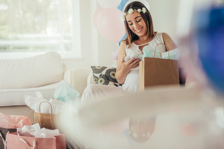 Expecting mother opening gifts received at baby shower