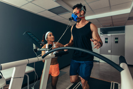 Athlete running on treadmill with female trainer